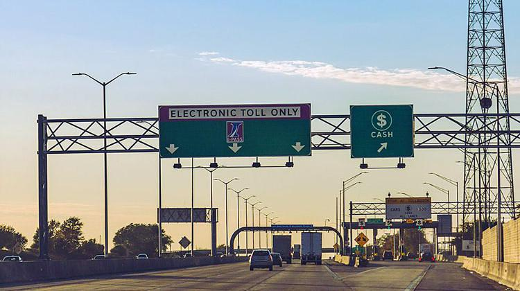 Traffic moves through an Illinois I-Pass electronic toll collection station. The Indiana Department of Transportation has hired a contractor to investigate all-electronic tolling on Indiana interstates.