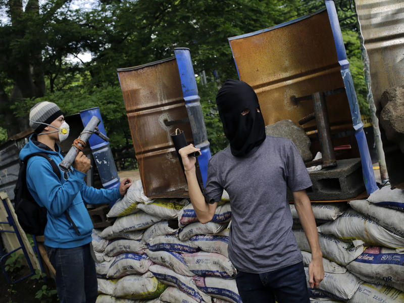 Students with homemade mortars stand guard behind makeshift shields and barricades Tuesday at the National University in Managua, which has been occupied by protesters for more than a month.