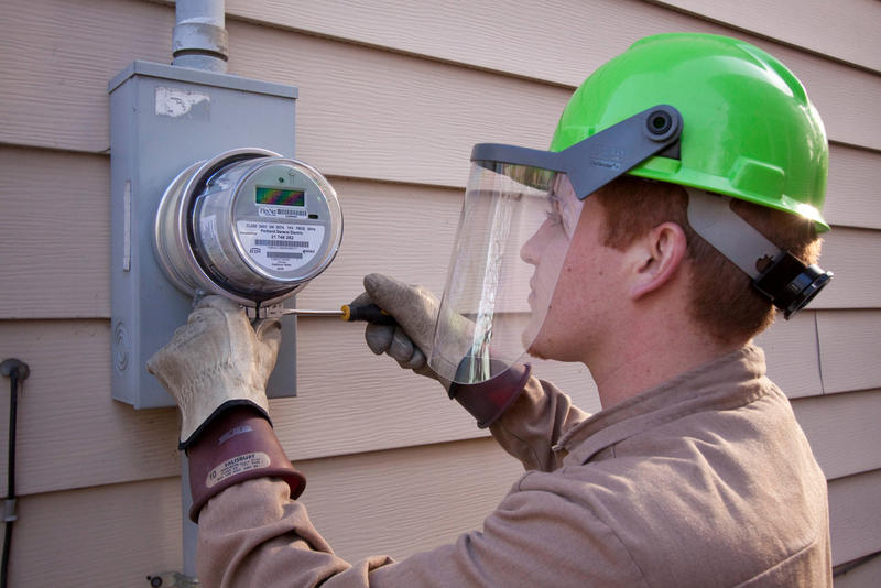 An employee of Wellington Energy Inc. works to install a new watthour meter at a residence in Portland, Oregon. (Portland General Electric)