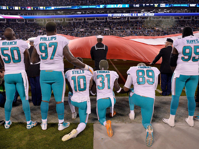 Miami Dolphins players kneel during the national anthem before their game against the Carolina Panthers at Bank of America Stadium on Nov. 13, 2017, in Charlotte, N.C.