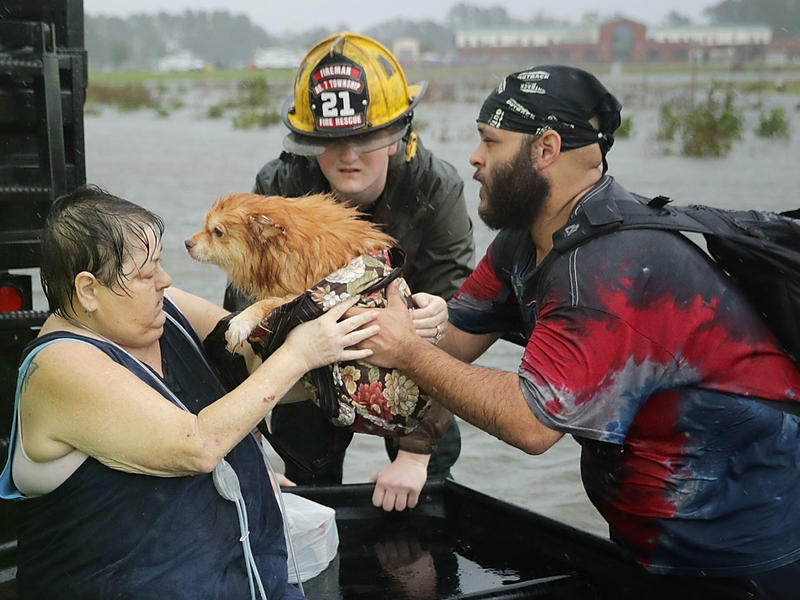 Rescue workers from Township No. 7 Fire Department and volunteers from the Civilian Crisis Response Team help rescue a woman and her dog from their flooded home during Hurricane Florence on Friday in James City, N.C.