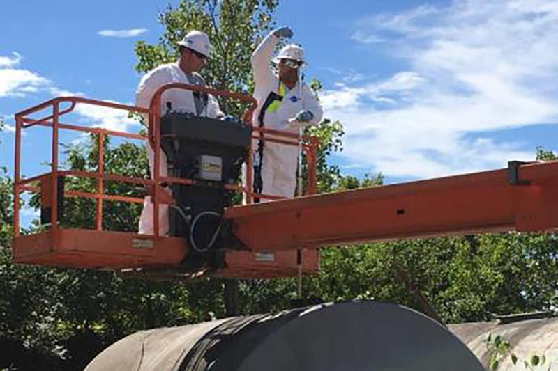 EPA contractors sample an above ground storage tank. (Photo courtesy EPA)