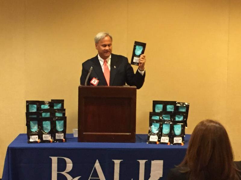 Sen. Jim Merritt (R-Indianapolis) shows a drug disposal kit at the Public Health Conference. (Jill Sheridan/IPB News)