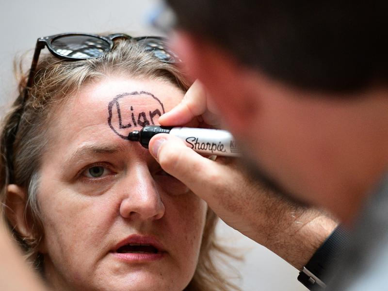 "An anti-Kavanaugh protester gets her face painted with the word ""liar"" Friday on Capitol Hill. The Senate narrowly voted to advance Brett Kavanaugh's nomination to the Supreme Court, but that has not dampened the determination of many protesters."