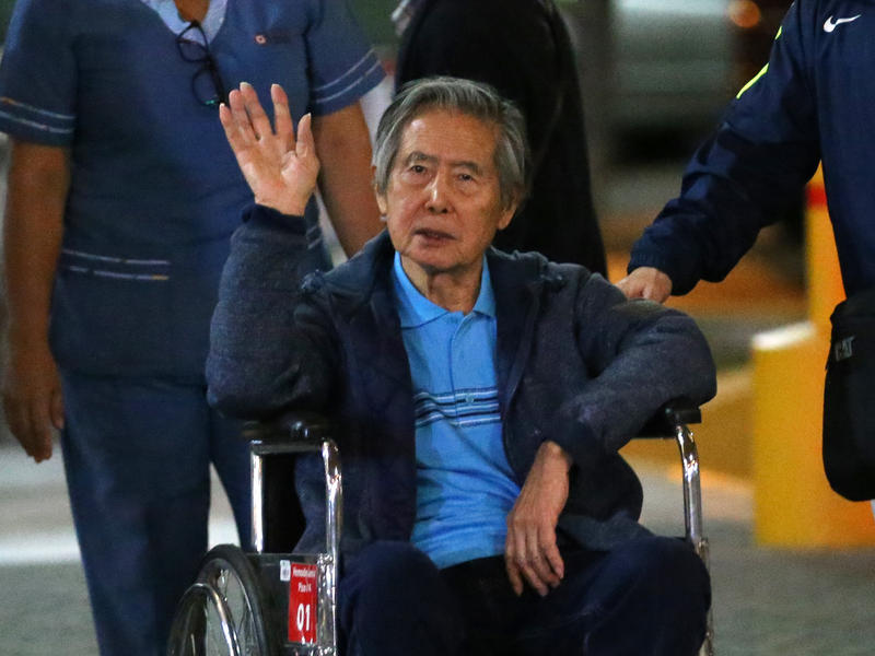 "Peru's former President Alberto Fujimori waves to supporters as he is wheeled out a clinic in January, after receiving a ""medical pardon."""