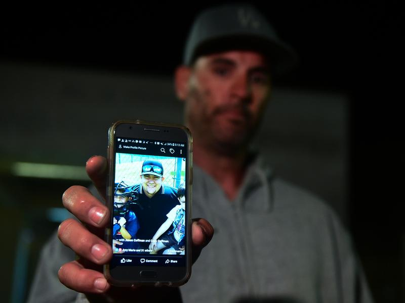 Jason Coffman displays a photo outside the Thousands Oaks Teen Center as he tried to locate his son Cody, who was later found dead at the Borderline Bar & Grill in Thousand Oaks, Calif.