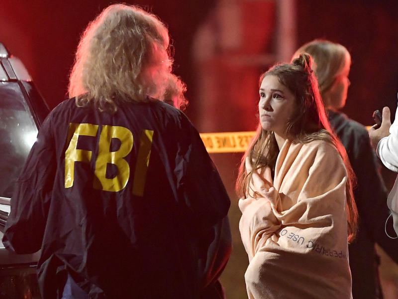 An FBI agent talks to a potential witness to the shooting at the Borderline Bar & Grill in Thousand Oaks, Calif., where a gunman opened fire inside the country dance bar on