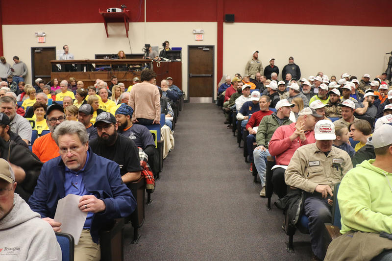 Community members gathered at hearing on an air quality permit for a proposed coal-to-diesel plant in Dale, Indiana. Opponents wore yellow shirts, union workers wore white caps as a show of support. (Isaiah Seibert/WNIN)