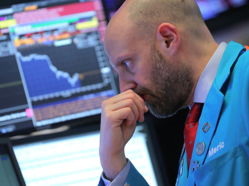 A trader works on the floor at the New York Stock Exchange on Tuesday, when the Dow Jones industrial average fell 799 points. Stock markets continued to fall on Thursday.