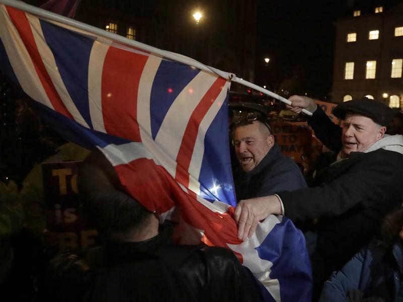 Brexit supporters and opponents shout at each other outside Parliament in London on Thursday, the day that British lawmakers voted to delay Brexit.