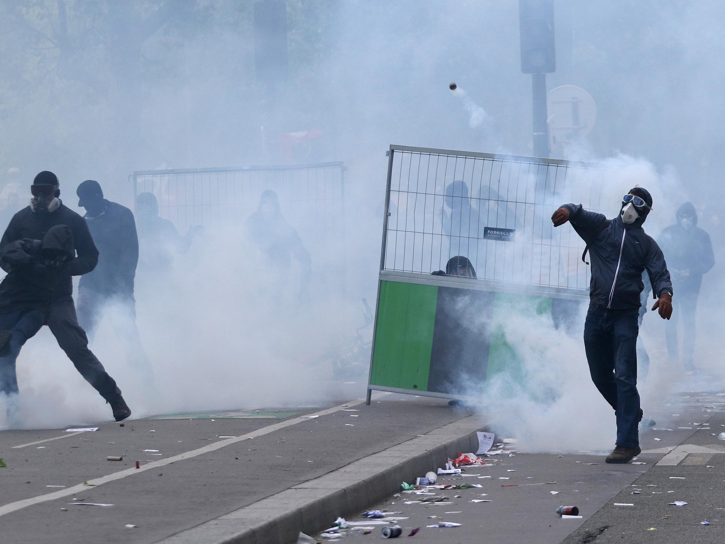 Masked protesters throw stones during clashes with French CRS riot forces at the May Day in Paris