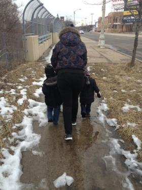 Mother and kids walking down a snowy sidewalk.