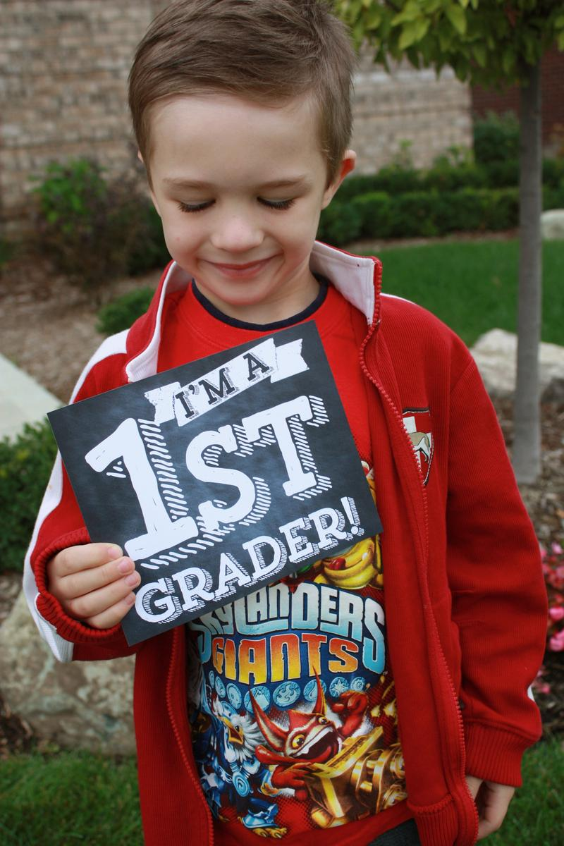 photo of child holding 1st grade sign