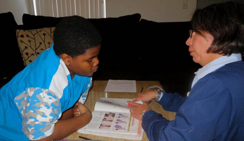 Mary Kim helps Jovon White with taking his asthma medication.
