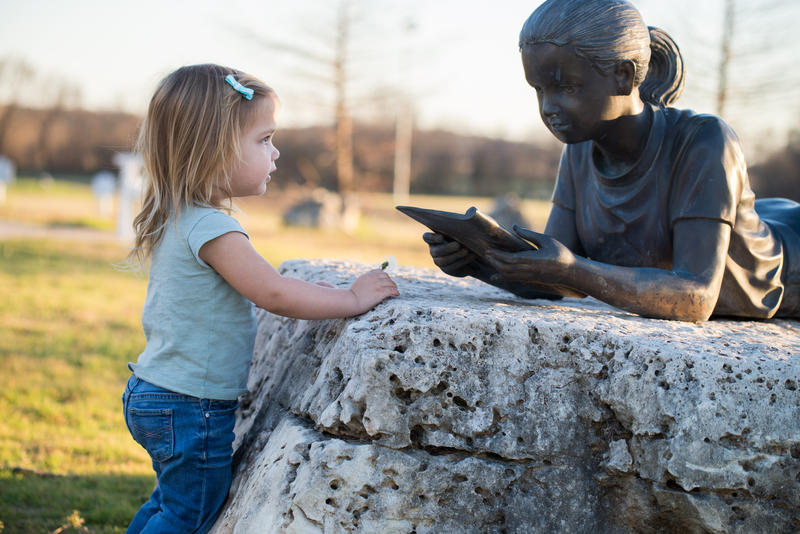 Girl with statue reading book