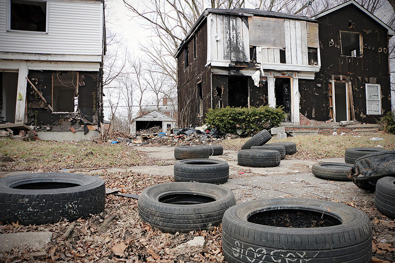 Tires litter the lawn in front of an abandoned house on Detroit's west side