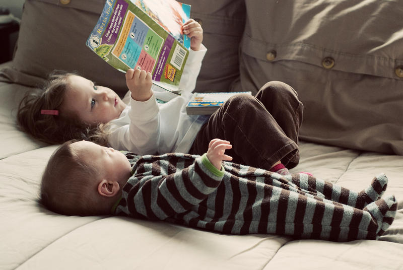 two young kids reading a book