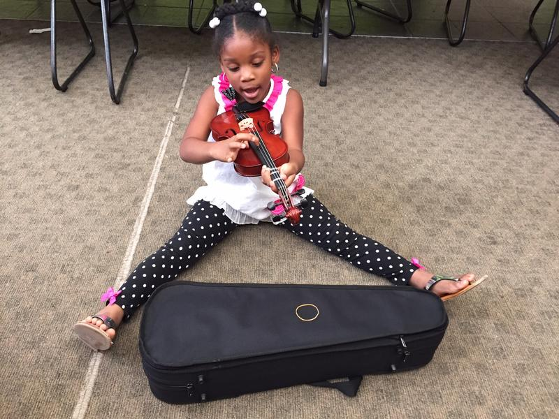 A young girl plucks out notes on the violin