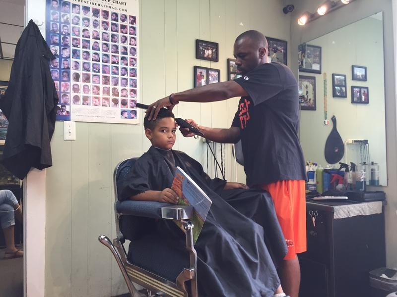 Jozef Jason, 7, reads to his barber