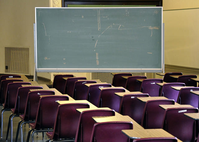 rows of desks in classroom facing chalkboard