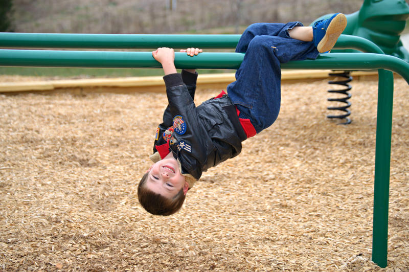 Kid hanging upside down at playground