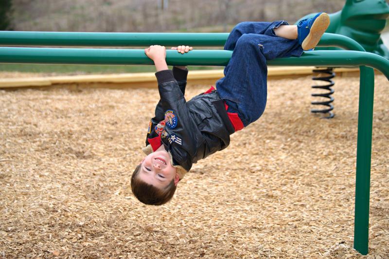 Kid hanging upside down at playground