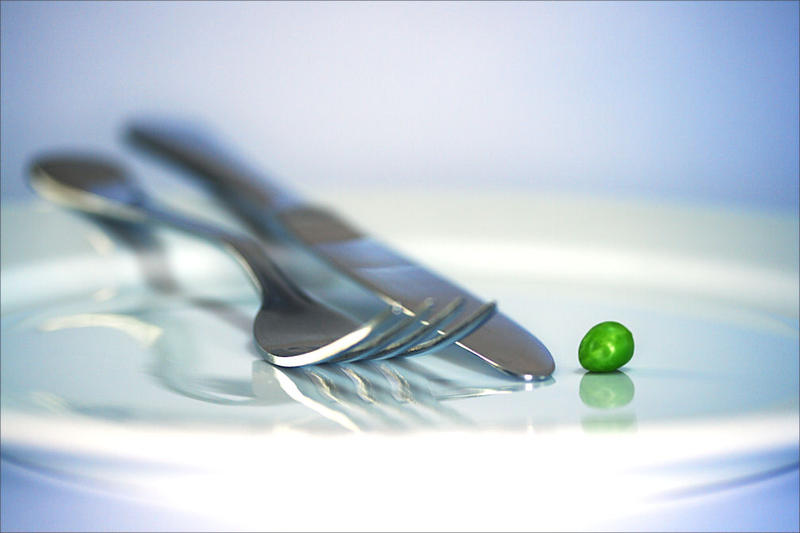 A pea on a plate. With a fork and knife.
