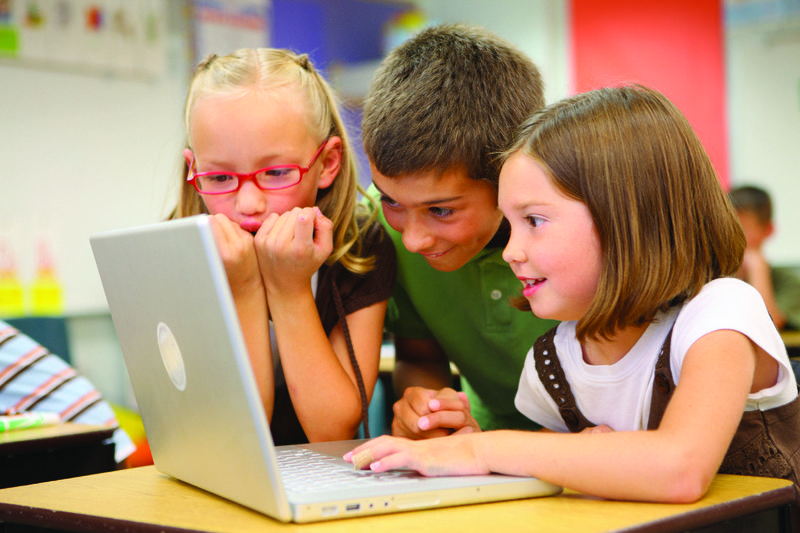 three kids using a laptop