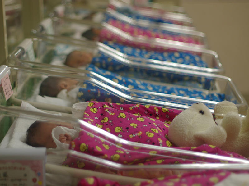 row of babies in hospital beds