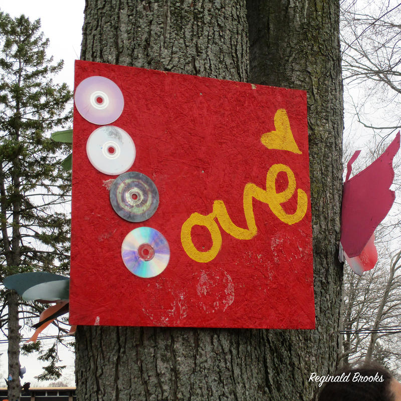red sign that says love nailed to tree
