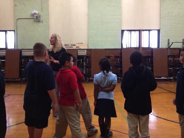 Congress principal Bridget Cheney directs kids in the gym.