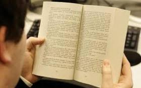 Image of open book held by person reading