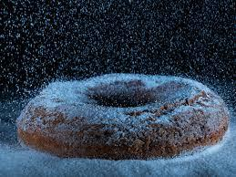 A doughnut with sugar falling on it