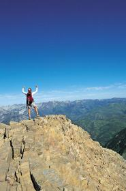 Person with arms raised on top of a mountain