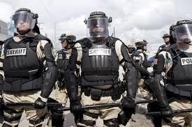 Policemen wearing body armor & helmets with faceshields