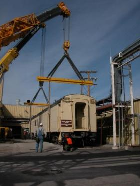 Cranes prepare to lift a 71-ton rail car from Deseret Chemical Depot during closure operations.