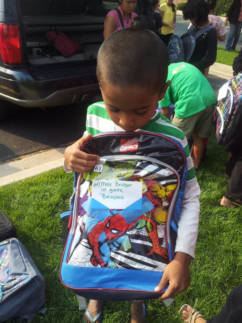 A Burmese refugee inspects his new backpack filled with supplies just in time for school to start.