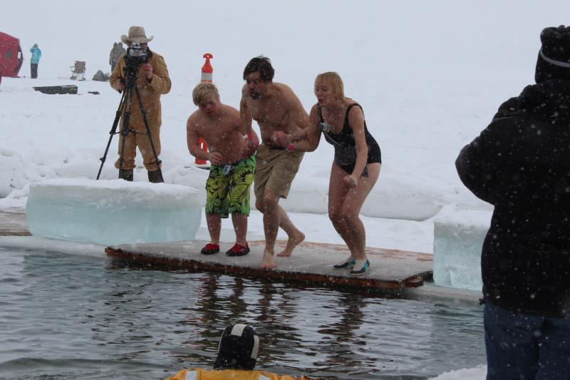 A young man with Down Syndrome jumps with his parents into the water.