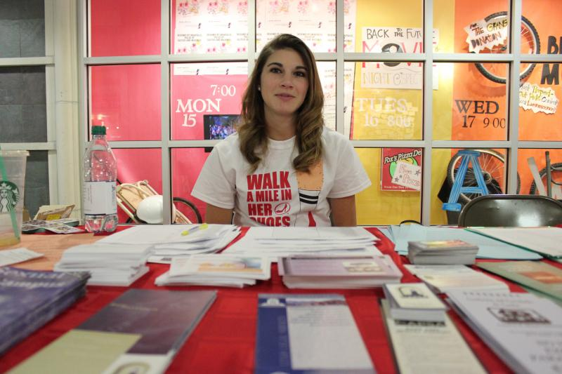 Whitney Rud sits at a table with information about sexual assault and rape in the Taggart Student Center.