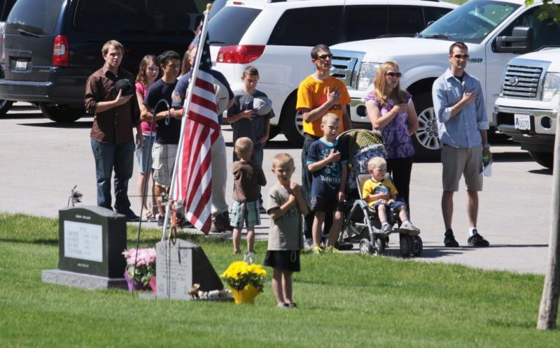"Family members join in to sing ""The Star Spangled Banner"" at the North Logan Cemetery on Monday."