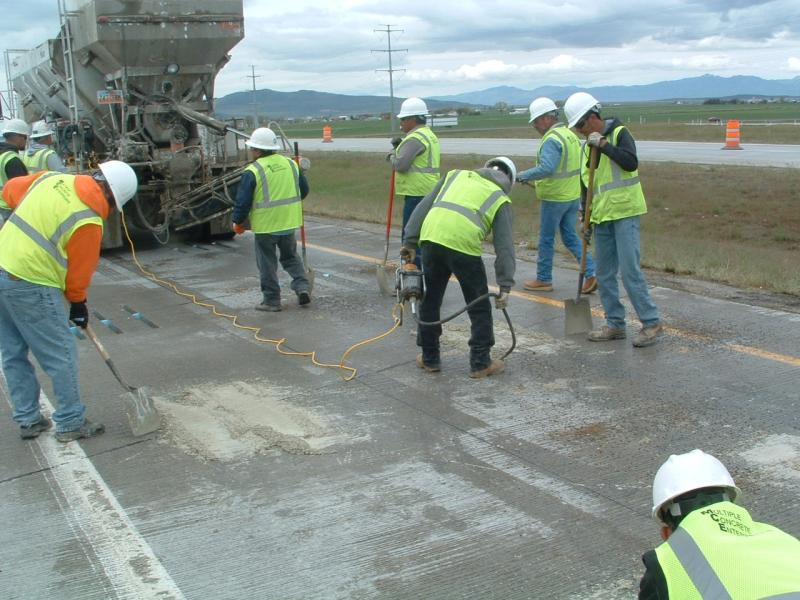Crews cover steel rods with cement.
