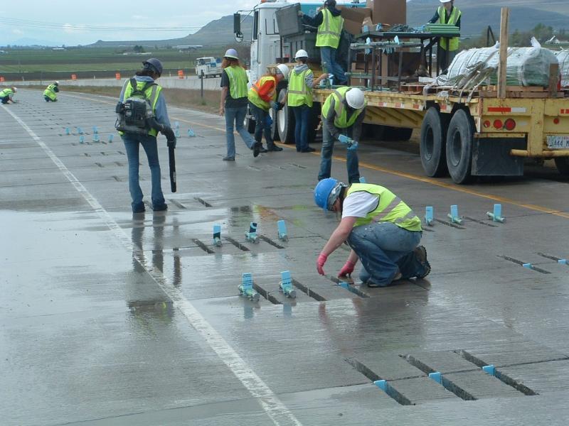 UDOT crews install steel dowels between concrete joints.