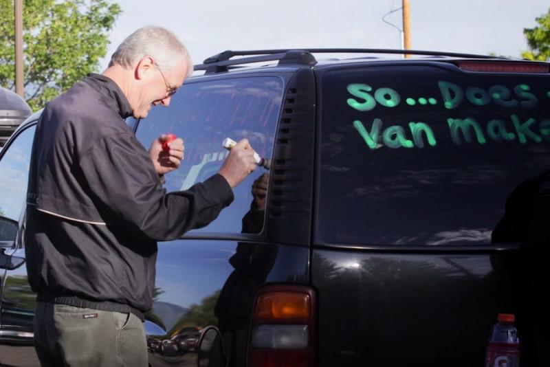 A participant writes his team name on a support vehicle prior to the relay event.
