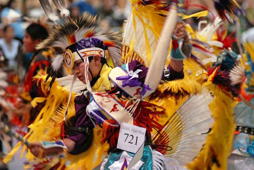 A Native American dancer in full regalia competing in a pow wow dance competition.