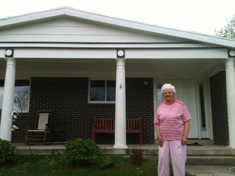 woman stands in front of house