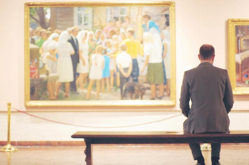 A man in a suit sits on a bench, with his back to the camera, looking on at a large painting on the wall.