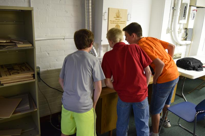 Students waiting for the laser wood cutter to finish a product.