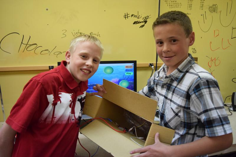 Students show off the wiring on their responsive videogame.