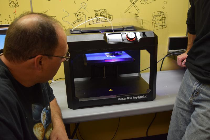 Mentors and students tinker with a finicky 3D printer.