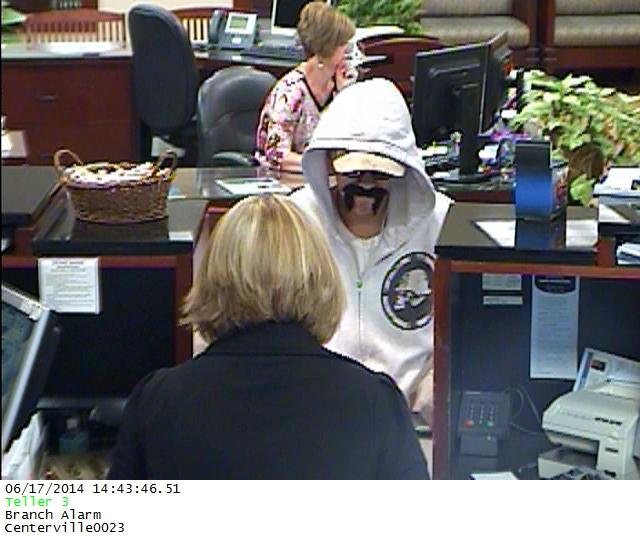 Surveillance still of mustache bandit robbing the bank.